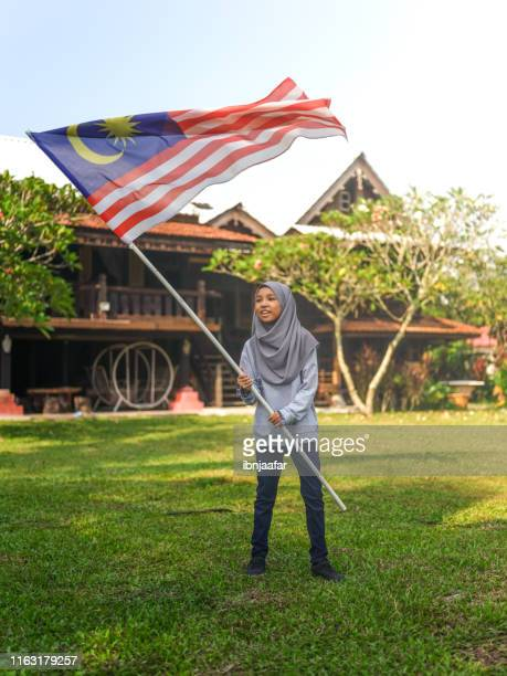 cute kids holding and waving national flag - ibnjaafar stock photos and pictures