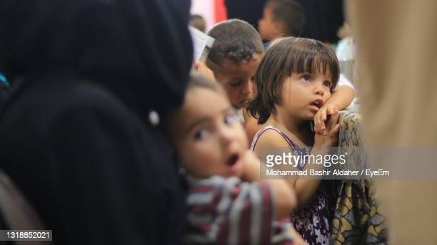 cute kids looking away while standing outdoors - refugee stock pictures, royalty-free photos & images