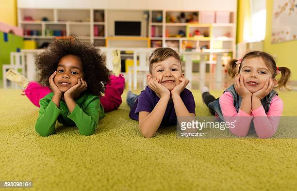 Cute kids lying on the floor at preschool and smiling.