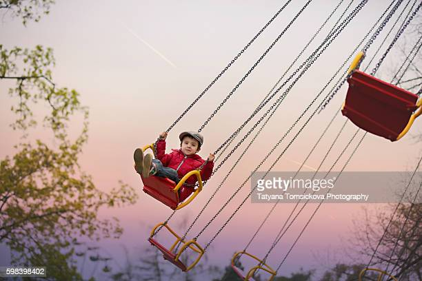 cute kids on a chain swing carousel, having fun - one boy only stock pictures, royalty-free photos & images