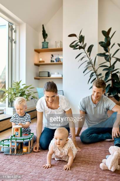 cute kids playing while sitting with parents - scandinavian culture stock pictures, royalty-free photos & images