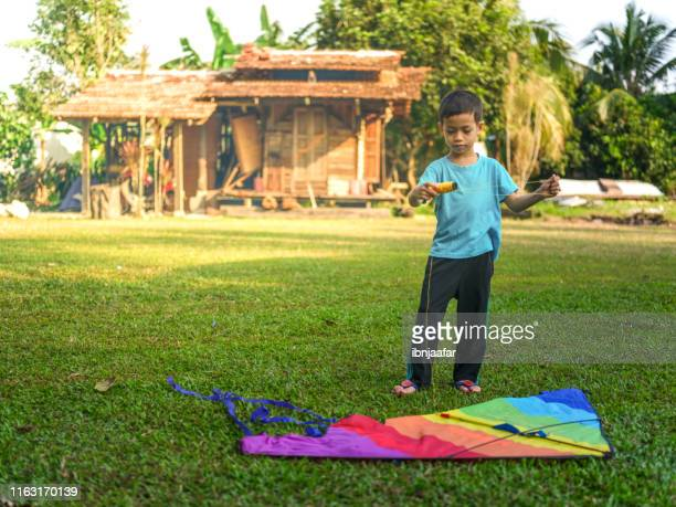 cute kids playing with kite - ibnjaafar stock photos and pictures