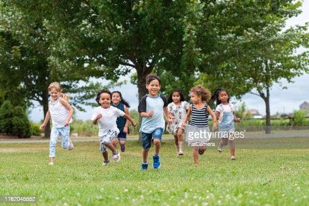 gosses mignons fonctionnant dehors dans la cour d'école - seulement des enfants photos et images de collection