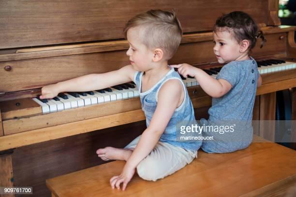 """niños lindos tratando de tocar el piano en casa. - """"martine doucet"""" or martinedoucet fotografías e imágenes de stock"""
