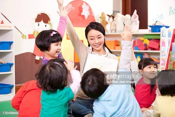 Cute kindergarten children raising hands to answer female teacher's question