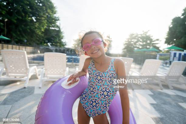 cute latin american 6 year old holding an inflatable ring outside the pool and wearing swimming googles looking at camera very cheerfully - kids swimsuit models stock pictures, royalty-free photos & images