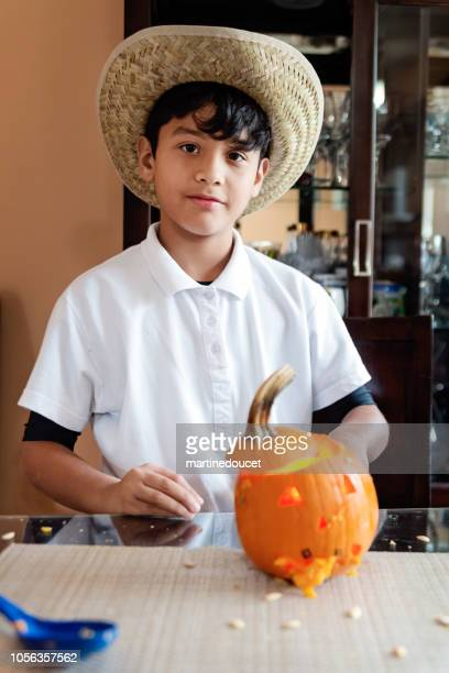 Cute Latin American boy showing his pumpkin for Halloween