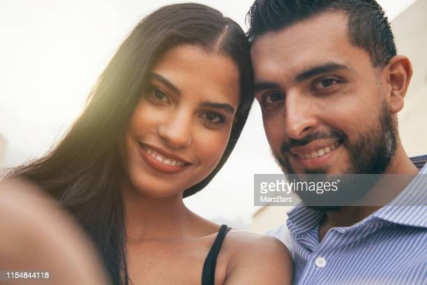 cute latino couple smiling at camera, selfie style - brown eyes stock pictures, royalty-free photos & images