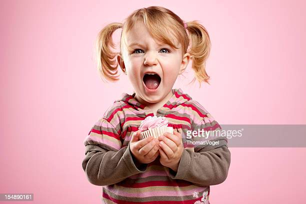 Cute litte girl dirty laughing and holding a pink muffin.