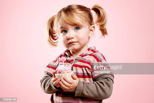 Cute litte girl holding pink birthday cupcake