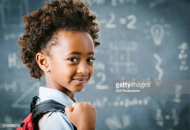 Cute little African school girl in classroom