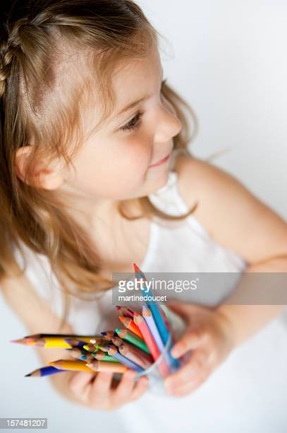 Cute little artist girl holding a pot of colourful crayons.