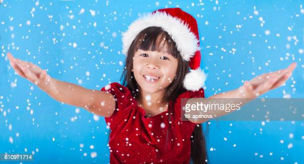 Cute little Asian girl catching snow flakes
