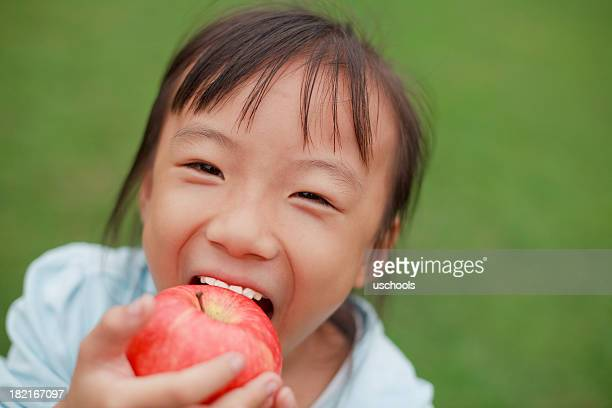 cute little asian girl eating apple - kid girl eating apple stock photos and pictures