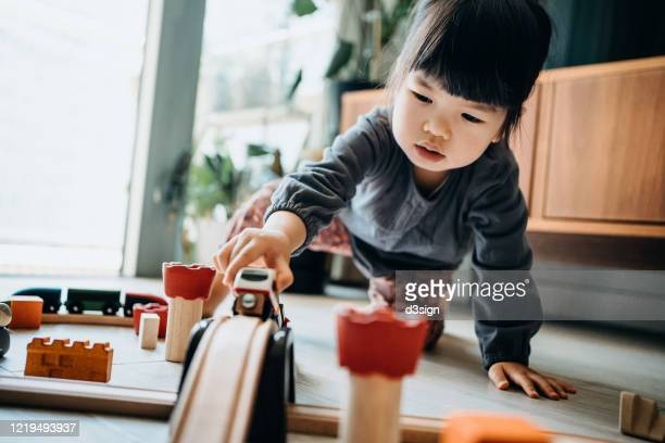 cute little asian girl playing with wooden toy train in the living room at home - toy stock pictures, royalty-free photos & images