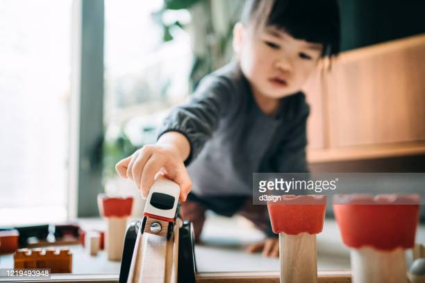 cute little asian girl playing with wooden toy train in the living room at home - シンプルな暮らし ストックフォトと画像