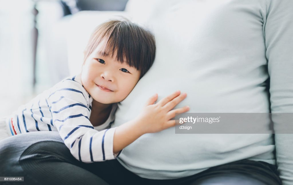 Cute little Asian girl touching and listening to pregnant mother's belly with joy : Stock Photo