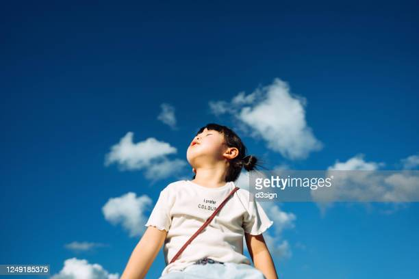 cute little asian girl with eyes closed enjoying the warmth of sun and the gentle breeze against beautiful blue sky on a lovely sunny day - innocence stock pictures, royalty-free photos & images
