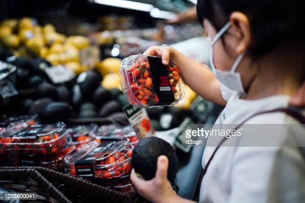 cute little asian girl with protective face mask grocery shopping in a supermarket. she is picking fresh organic avocado and a box of goji berries in the produce aisle - organic stock pictures, royalty-free photos & images