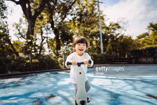cute little asian toddler girl having fun and riding a scooter joyfully in the park - toddler stock pictures, royalty-free photos & images