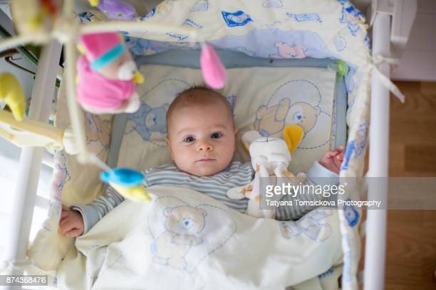 Cute little baby boy, playing in crib in the afternoon
