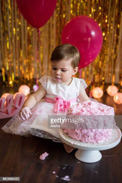 Cute little baby girl celebrating her birthday with smash cake