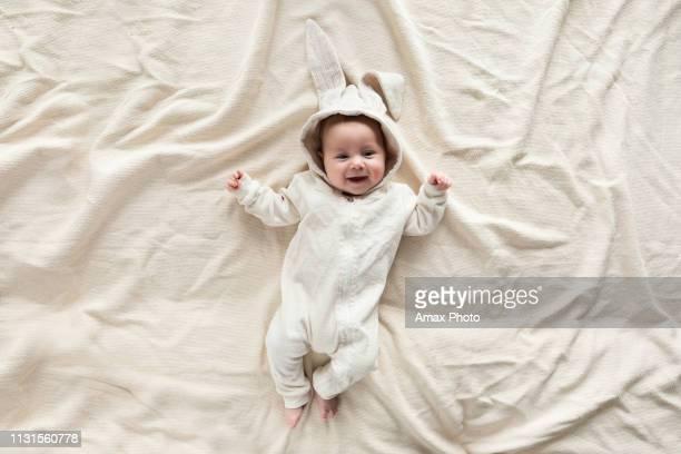 lindo bebé en traje de conejito en manta en casa, vista superior - monada fotografías e imágenes de stock