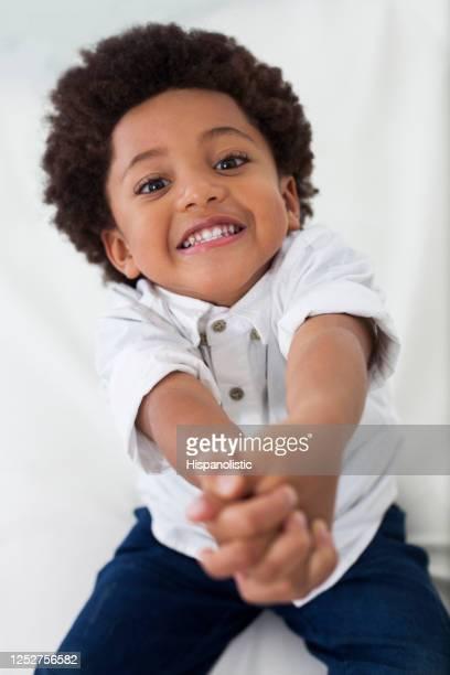 カメラの笑顔に直面しながら嘆願かわいい黒い男の子 - 懇願する ストックフォトと画像