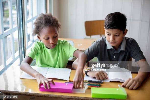 cute little black girl and mixed race boy coloring with crayons during class - south america stock pictures, royalty-free photos & images