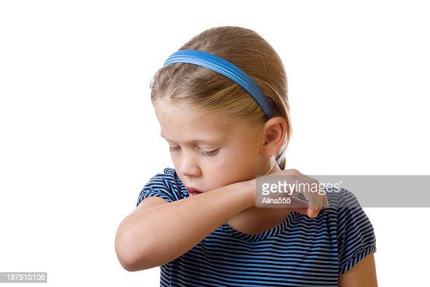 Cute little blond girl coughing in her elbow on white