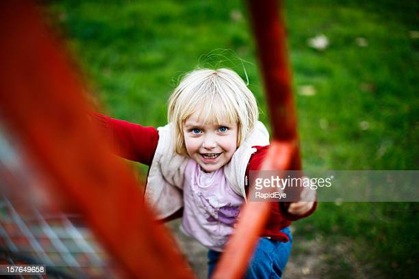 Cute little blonde girl plays happily on playground slide