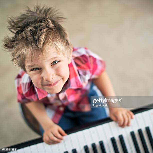 Cute little boy aged 4 playing piano