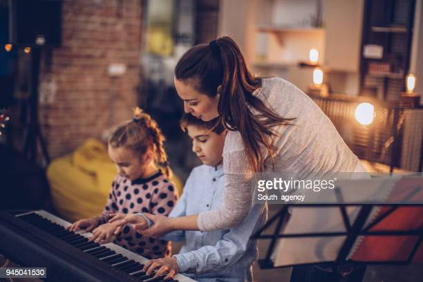 Cute little boy and girl teaching to play piano