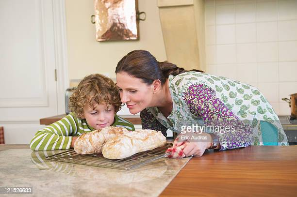 Cute little boy and mother smelling baked bread
