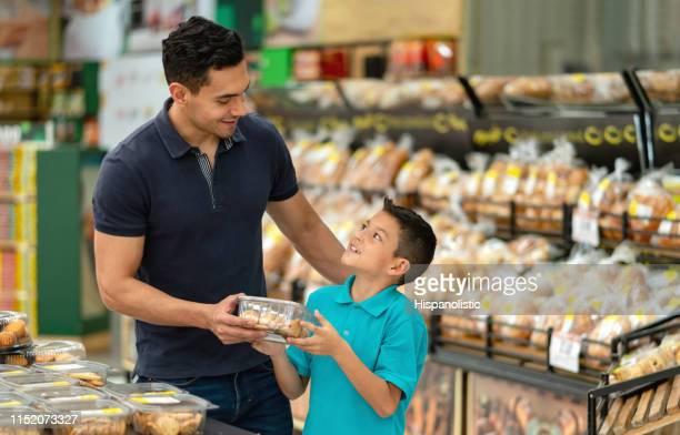 rapaz pequeno bonito que pede seu paizinho para comprar uma caixa dos bolinhos na seção da padaria do supermercado - comida pronta - fotografias e filmes do acervo