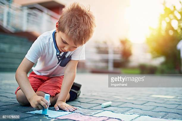 cute little boy chalking on street - chalk drawing stock pictures, royalty-free photos & images