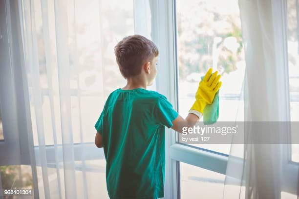 cute little boy cleaning windows - kids with cleaning rubber gloves stock pictures, royalty-free photos & images