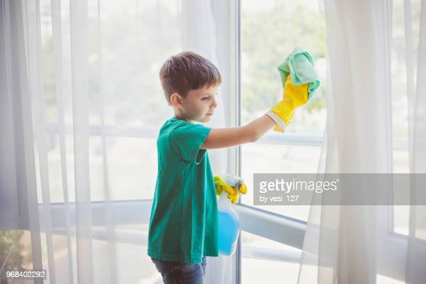 cute little boy cleaning windows - chores stock pictures, royalty-free photos & images