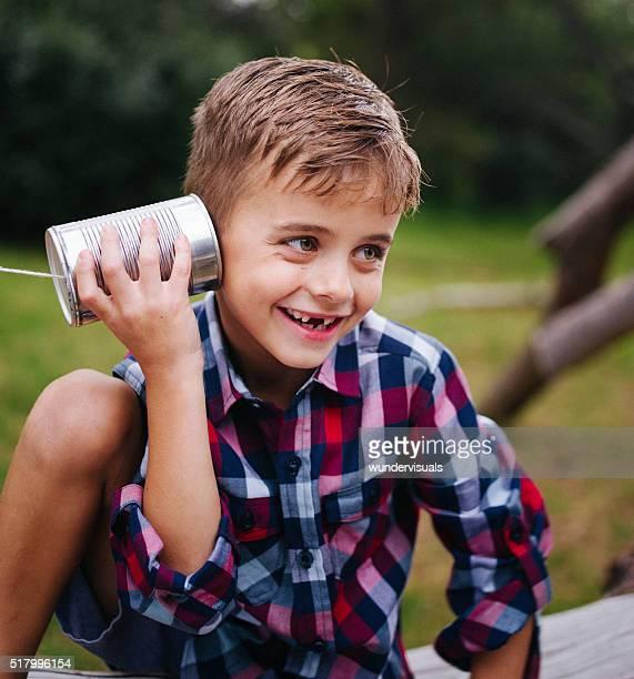 Niedlich kleine Junge merkwürdig anhören Dosentelefon im Park