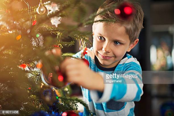 Cute little boy decorating christmas tree