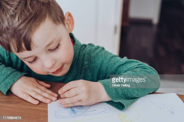 cute little boy drawing a picture on white paper sheet - alleen jongens stockfoto's en -beelden