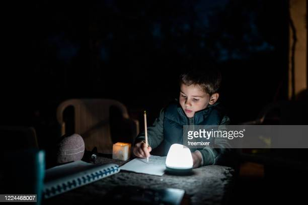 menino bonito desenhando no quintal em lâmpada elétrica de baixa luz - lanterna - fotografias e filmes do acervo