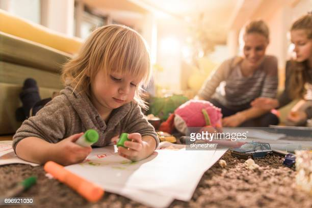 Cute little boy drawing on a paper while relaxing on the floor at home.