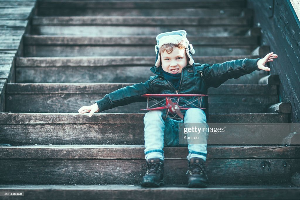 Cute little boy dreaming of becoming a pilot : Stock Photo