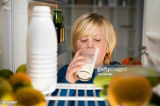 Cute little boy drink milk in fridge at the night