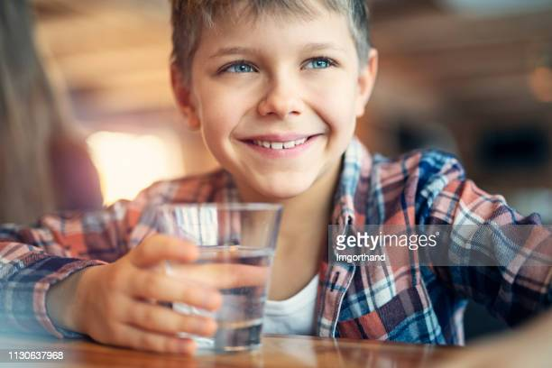 cute little boy drinking a glass of water - drink water stock pictures, royalty-free photos & images