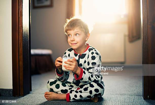 Cute little boy drinking glass of milk in morning