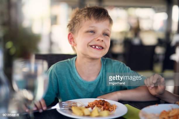Schattige kleine jongen eten van maaltijd in restaurant