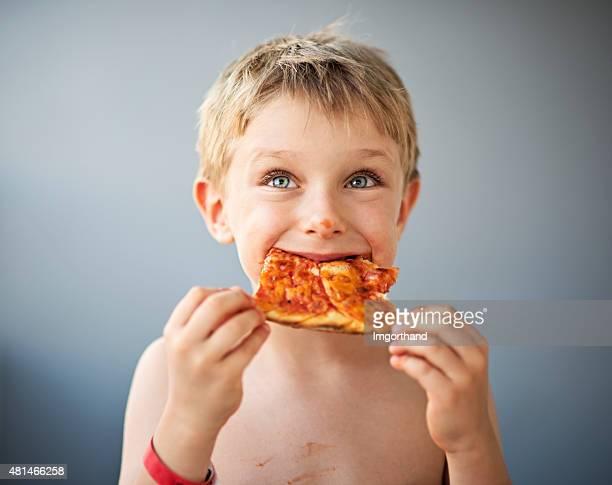 Cute little boy eating pizza