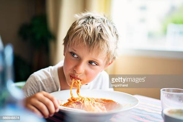 Cute little boy eating spaghetti
